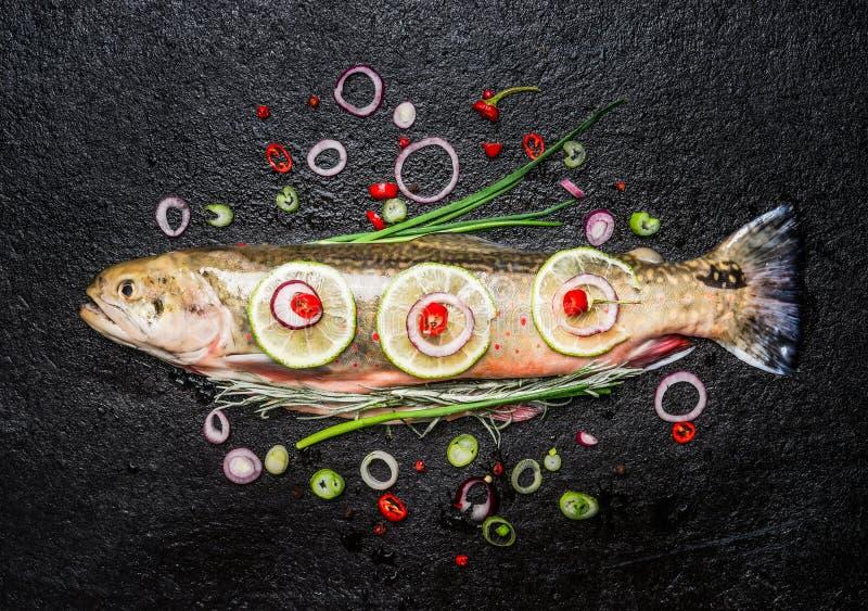 Pesce fresco con condimento tagliato delizioso pronto per la cottura saporita sul fondo scuro, vista superiore immagini stock
