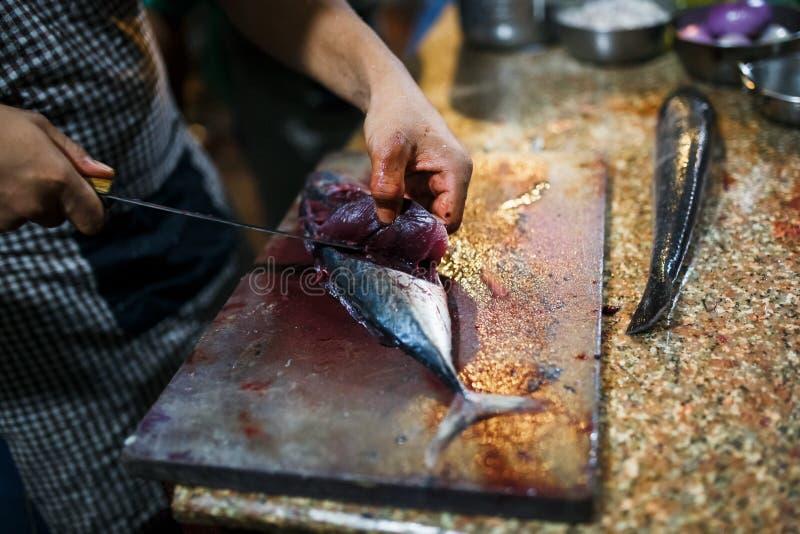 Pesce fresco di taglio del cuoco unico nel mercato ittico a mano con un coltello tagliente su un tagliere Sushi, cena, pranzo Ali fotografia stock