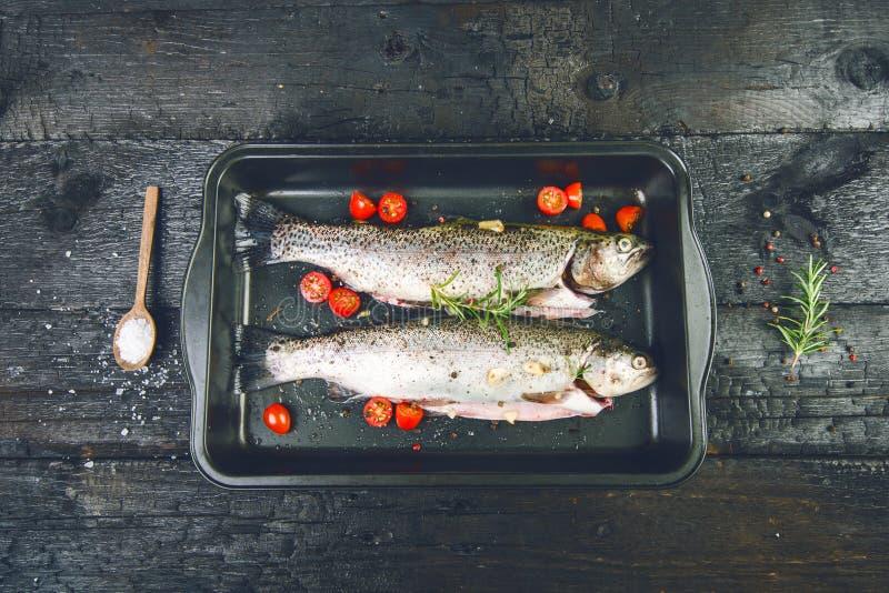 Pesce fresco su una tavola nera e bruciata d'annata Tabella di legno Peschi con le verdure, il sale, l'olio, erbe Concetto di cot fotografie stock libere da diritti