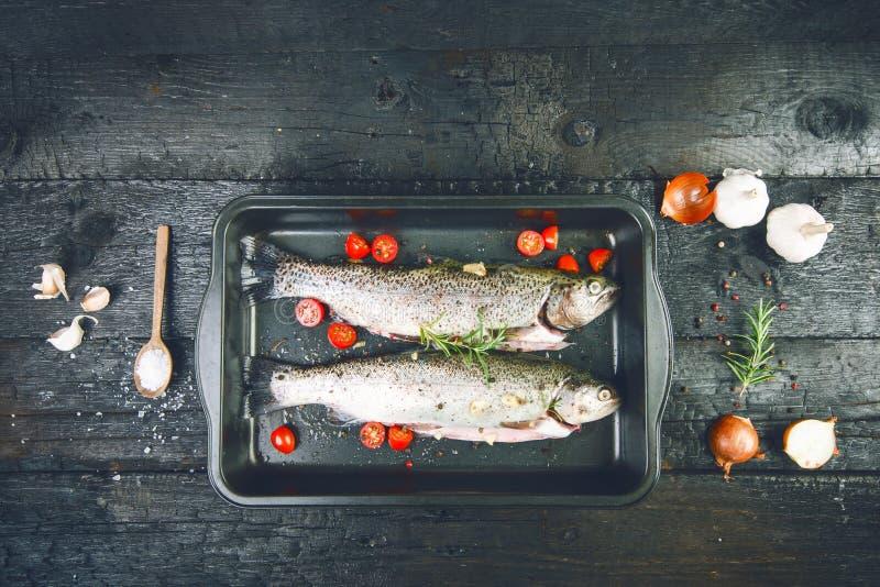 Pesce fresco su una tavola nera e bruciata d'annata Tabella di legno Peschi con le verdure, il sale, l'olio, erbe Concetto di cot fotografia stock