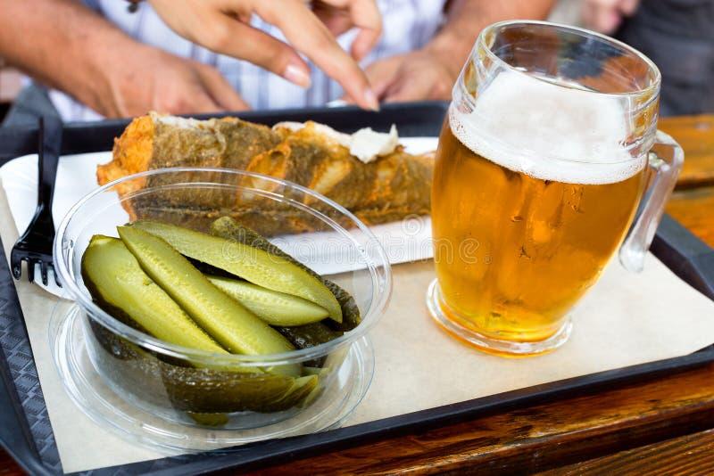 Pesce fritto delizioso, cetrioli marinati e vetro raffreddato della birra alla spina su un vassoio sulla tavola di legno in caffè fotografie stock libere da diritti