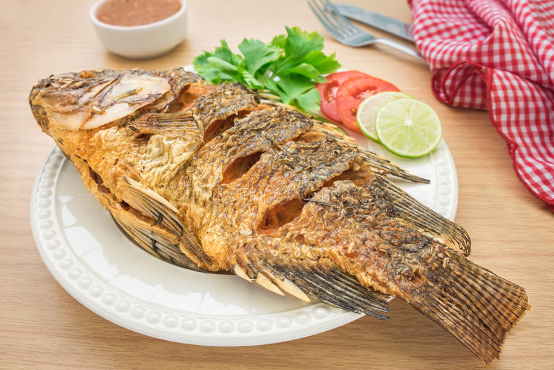 Pesce fritto sul piatto e sulla salsa bianchi della immersione fotografia stock libera da diritti