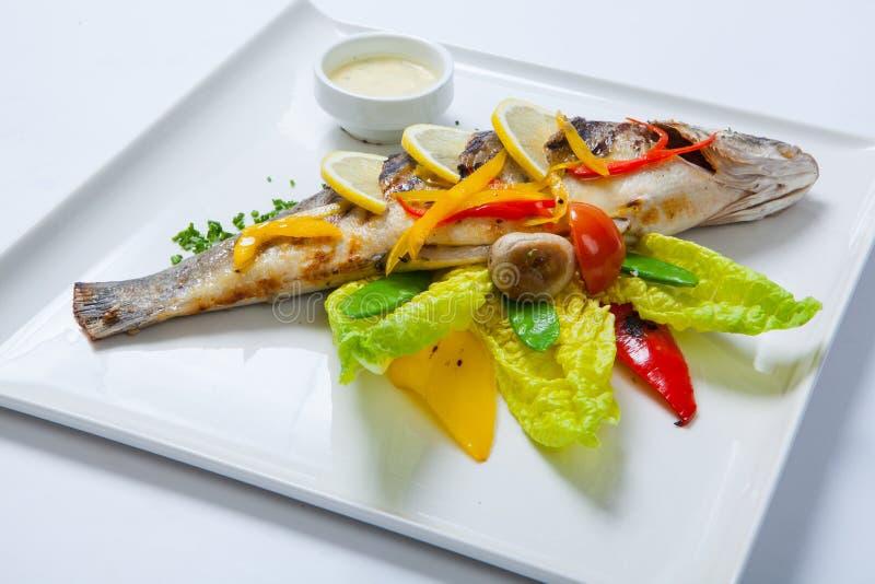 Pesce intero arrostito decorato con le foglie di lattuga e del pomodoro ciliegia, servite con la salsa di aglio Pesce intero frit immagine stock libera da diritti