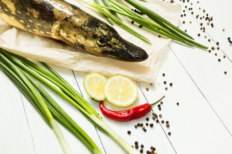 Pesce organico del fiume fresco - luccio su una tavola di legno bianca con le spezie Alimento dietetico e sano immagini stock