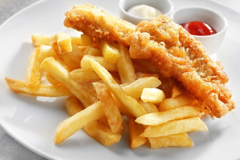 Pesce, patatine fritte e salse fritti saporiti sul piatto fotografia stock libera da diritti