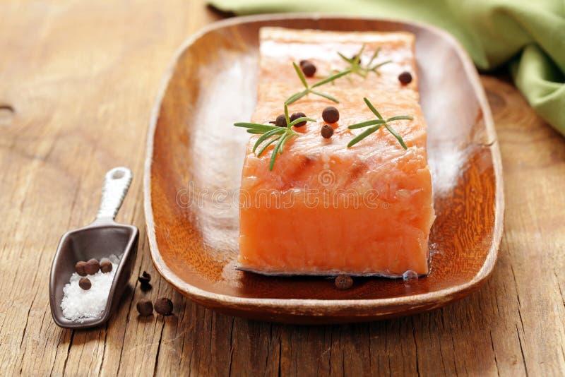 Pesce rosso di color salmone salato con pepe nero fotografia stock libera da diritti