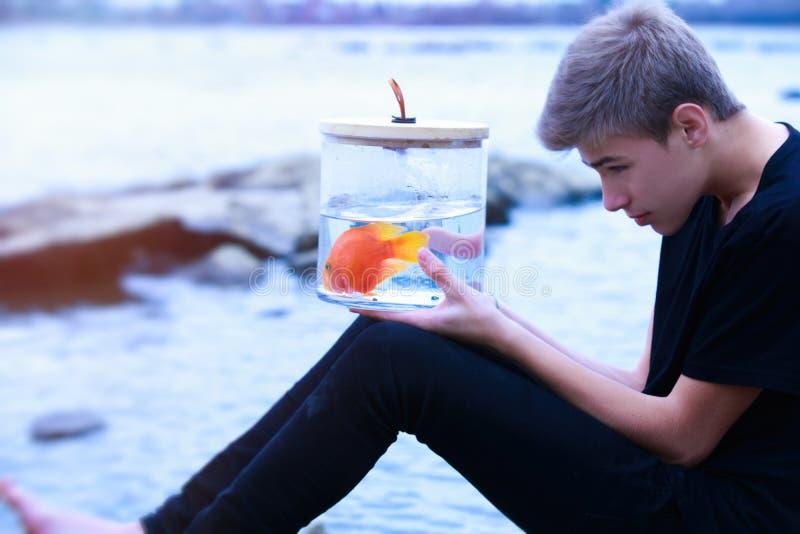 Pesce rosso in una borsa nelle mani di un adolescente sulla spiaggia immagine stock