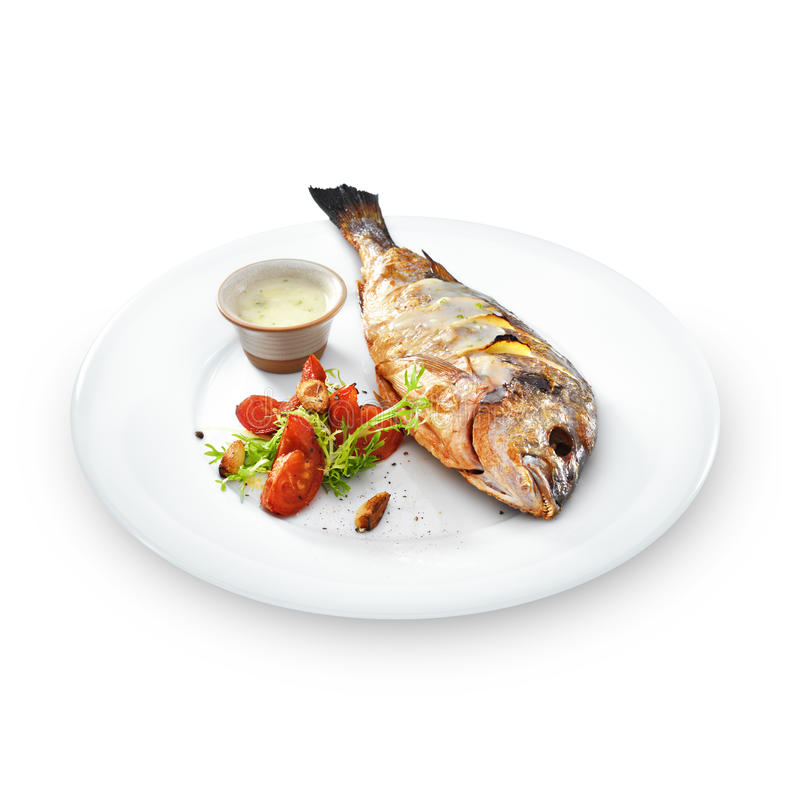 Pesce sano arrostito di dorado con le verdure su un piatto rotondo fotografia stock