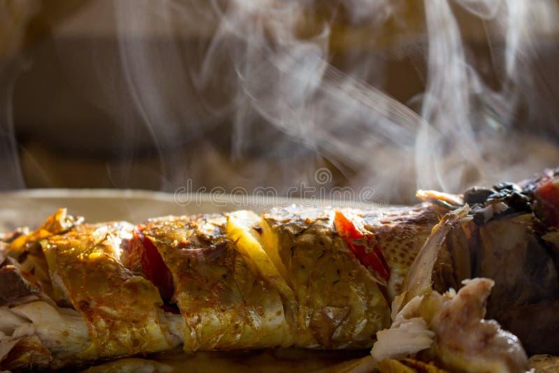 Pesce saporito fritto con il limone ed il pomodoro con fumo Pesce arrostito con la crosta crisry e fumo retro Pesce delizioso nel fotografie stock