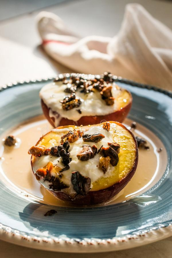 Pesche cotte con yogurt greco, le noci ed il miele arrostito/nettarine fotografia stock libera da diritti