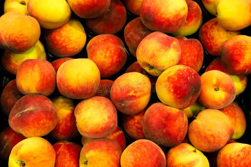 Pesche fresche o nettarine rosse e gialle prunus persica su un canestro di frutta da vendere in bio- supermercato o drogheria fotografie stock