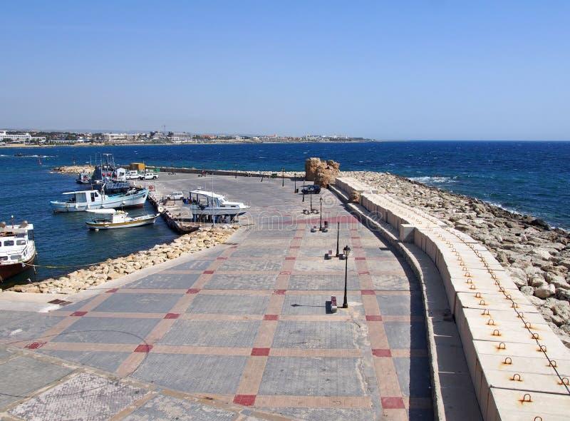 pescherecci e yacht attraccati lungo la vecchia parete del porto di Pafo con una vista delle costruzioni e della città fronte mar fotografie stock