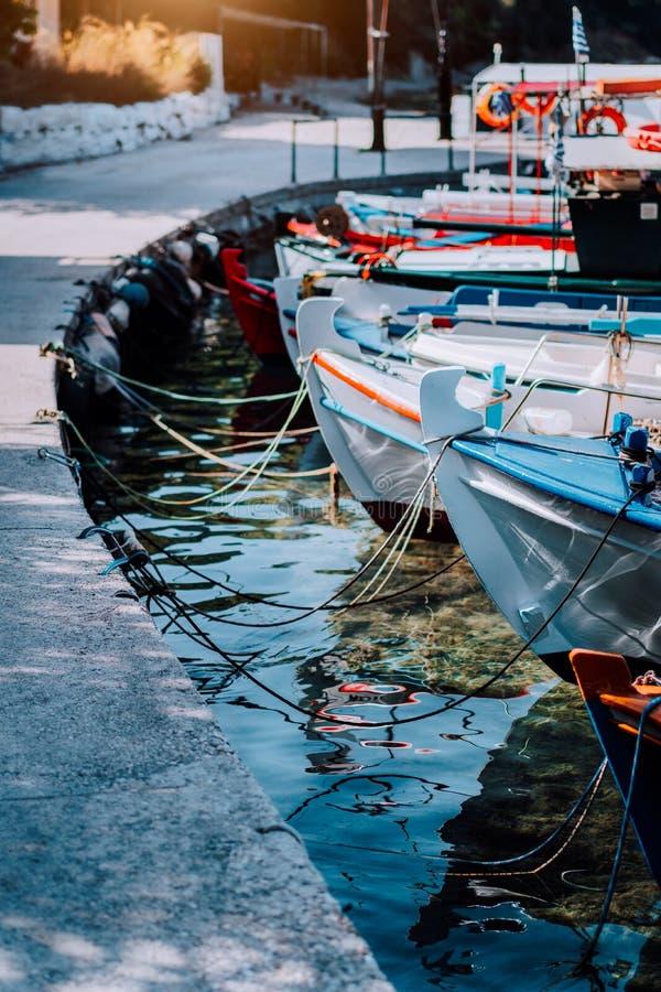Pescherecci variopinti messi in bacino di fianco vicino alla banchina sulla costa scena dell'isola greca, mar Mediterraneo fotografie stock