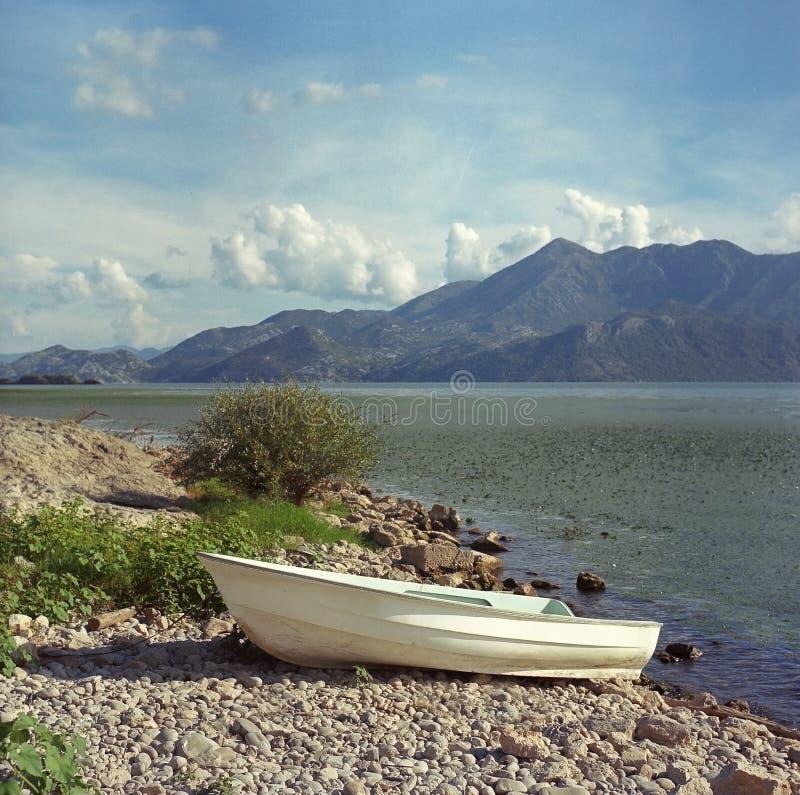 Peschereccio bianco sulla costa del lago Skadar montenegro Foto del film 25 agosto 2016 fotografie stock