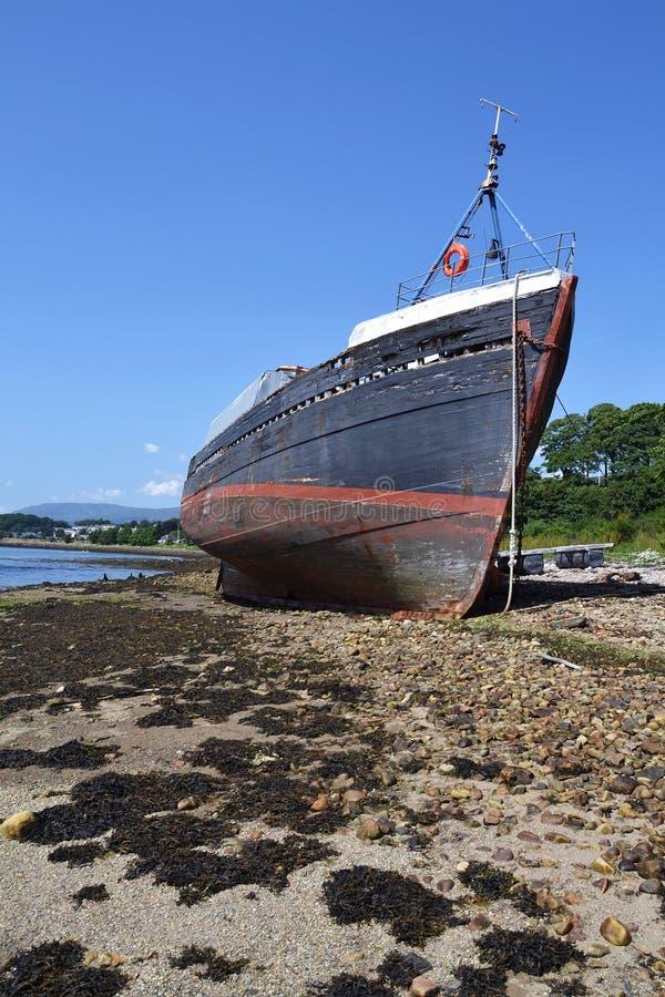 Peschereccio d'annata abbandonato sulla spiaggia vicino al villaggio di Corpach, Fort William, Scozia, Regno Unito immagini stock