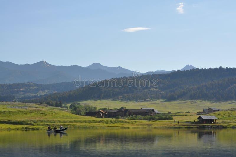 Peschereccio sullo stagno nelle montagne immagini stock
