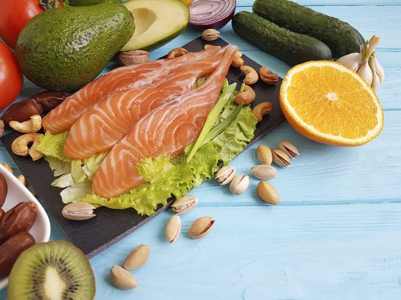 Peschi l'avocado di color salmone di Omega 3 sull'alimento sano del fondo di legno blu fotografia stock
