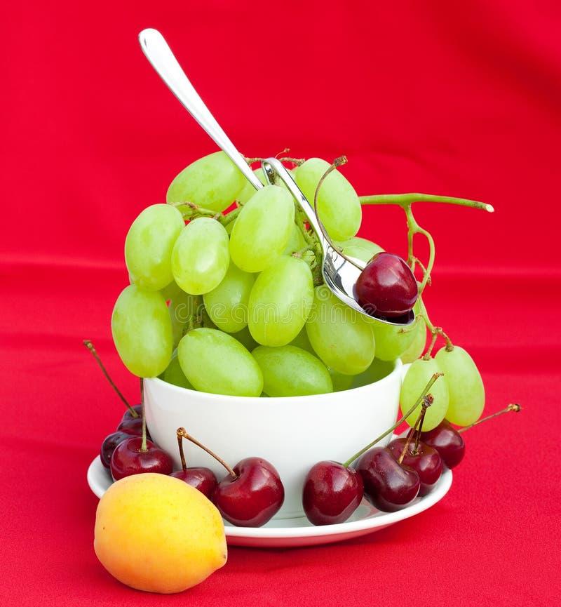 Peschi l'uva ciliegia ed albicocca nella tazza immagine stock