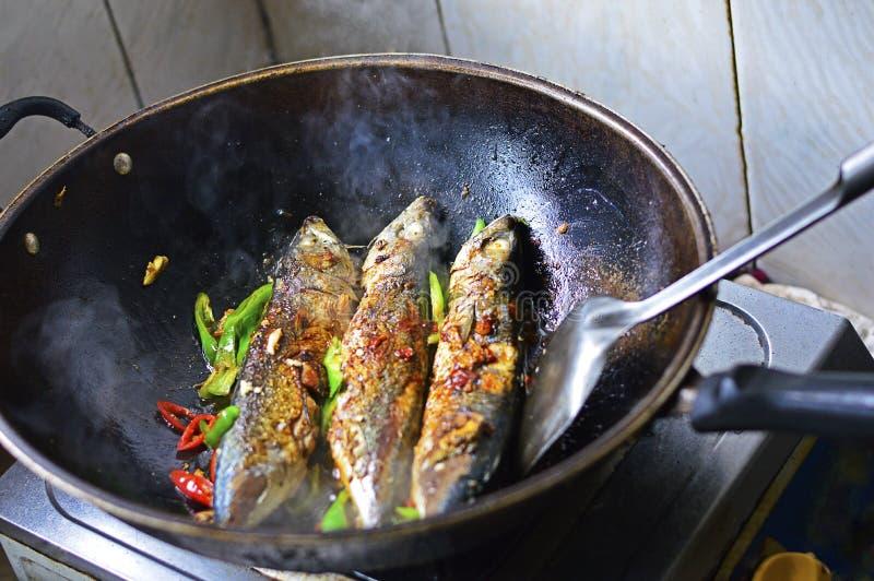 Pesci cinesi di cottura domestica fritti in un wok con i peperoncini rossi verdi e rossi immagine stock libera da diritti