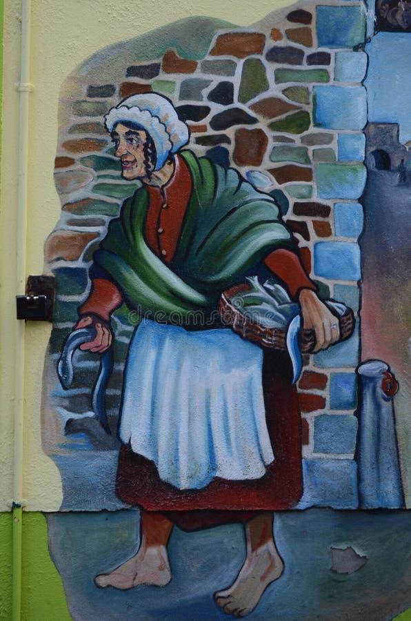 Pesci di trasporto della donna, pittura celtica su una parete sulle vie di Galway, Irlanda fotografia stock libera da diritti