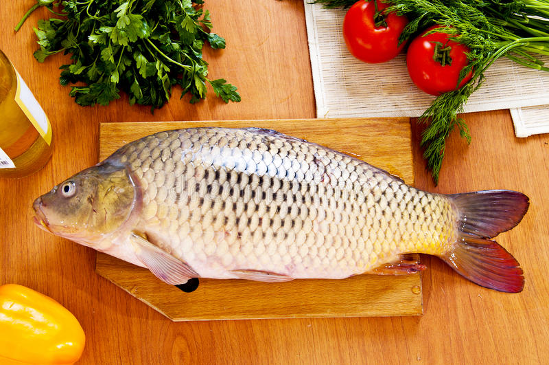 Pesci freschi (carpa) con le verdure immagini stock libere da diritti