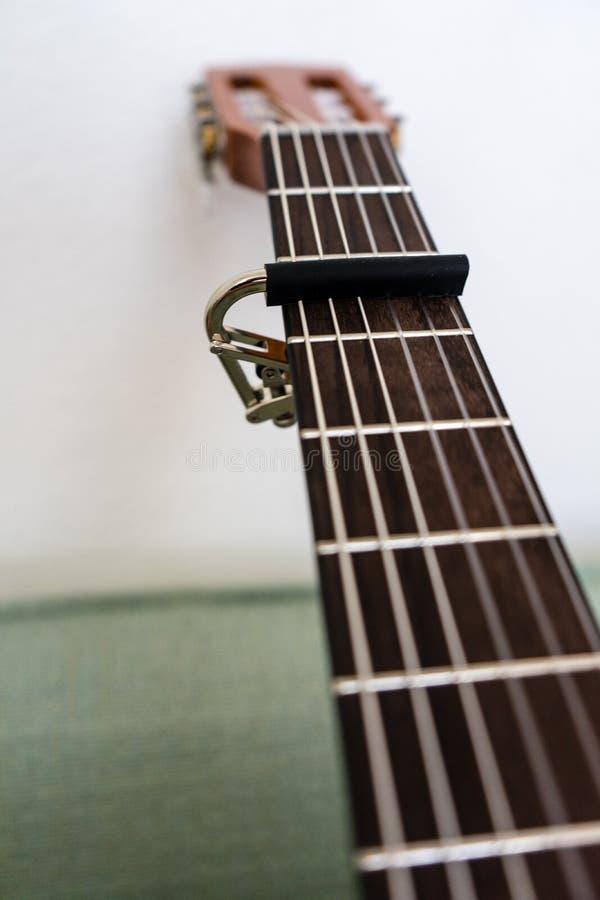 Pescoço da guitarra com fim da opinião de baixo ângulo do capo acima imagens de stock royalty free