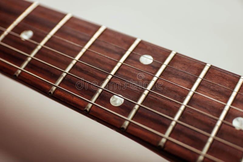 Pescoço e cordas da guitarra próximos acima da vista superior no fundo branco imagem de stock