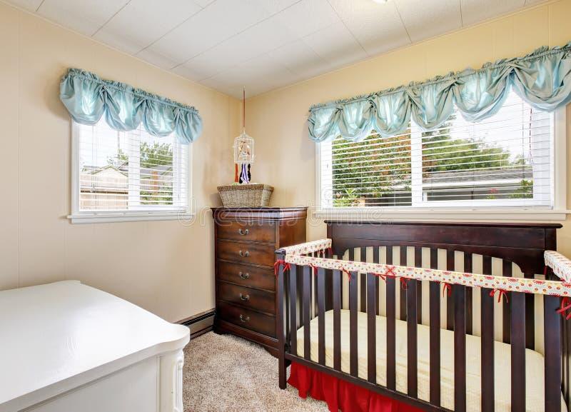 Pesebre de madera del bebé de la cereza en interior del cuarto de niños con la moqueta fotografía de archivo libre de regalías