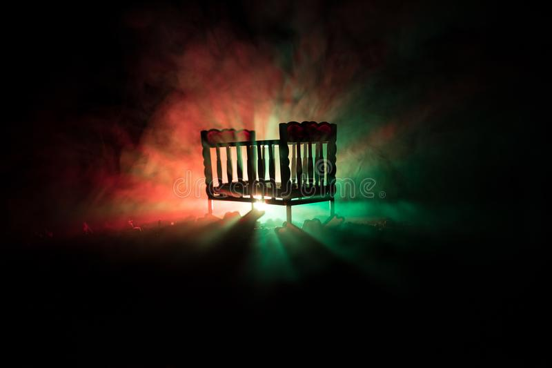 Pesebre de madera misterioso espeluznante viejo del bebé en fondo de niebla entonado oscuro Concepto del horror Silueta asustadiz foto de archivo