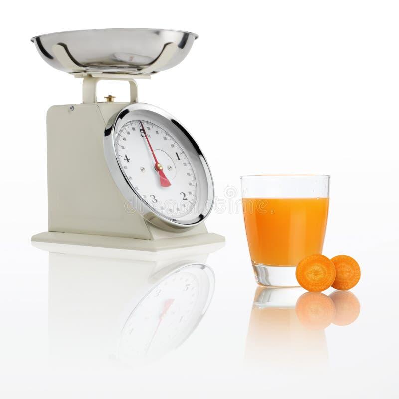 Pesez l'échelle avec le verre de jus de carotte d'isolement sur le backgroun blanc photo libre de droits