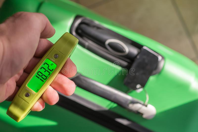Pesez la valise avec une échelle de bagage images libres de droits