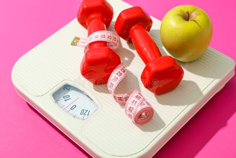 Pesez les échelles, la pomme, les haltères et la bande de mesure images stock