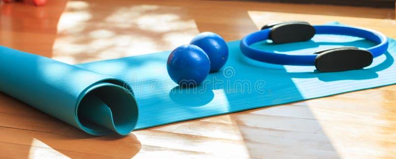 Pesi della stuoia e di esercizio di yoga sul pavimento di legno immagine stock
