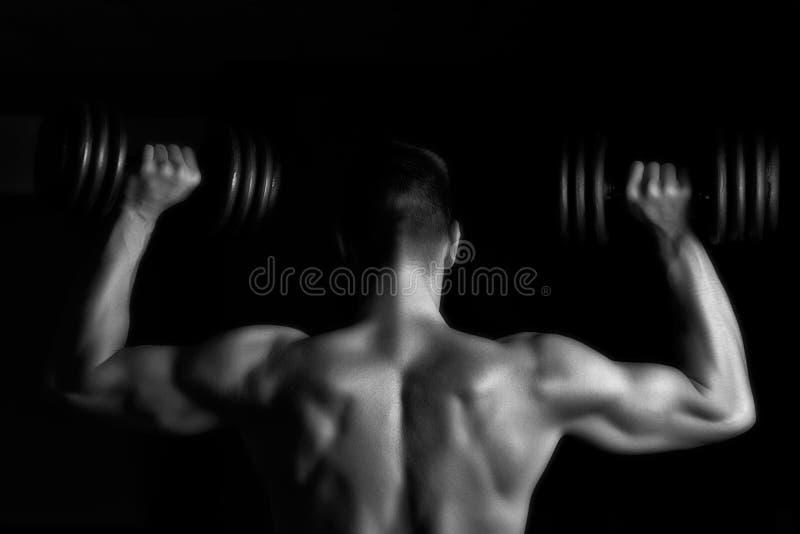 Pesi di sollevamento del giovane uomo muscolare bello immagine stock libera da diritti