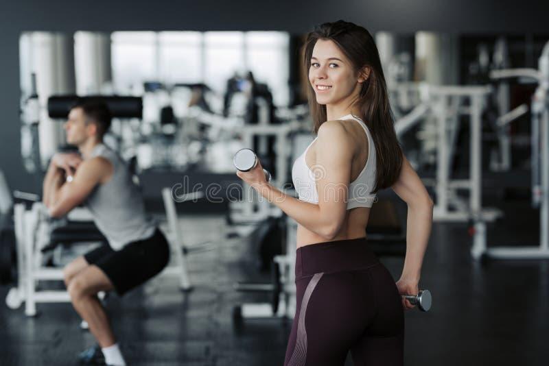Pesi di sollevamento della giovane sportiva in abiti sportivi d'uso della palestra con il suo ragazzo su fondo fotografie stock