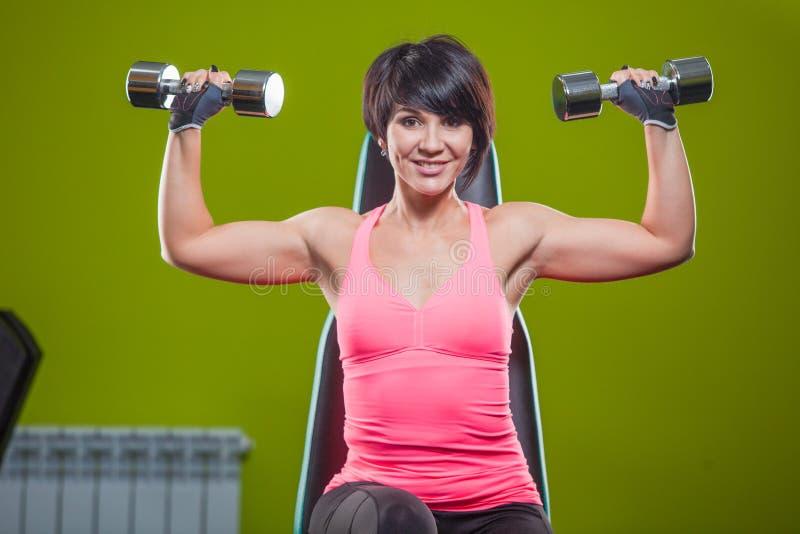 Pesi di sollevamento della testa di legno di addestramento di forza della donna della palestra nell'esercizio della stampa della  immagini stock