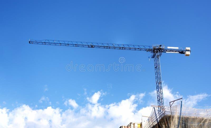 Pesi di sollevamento di una gru su un cantiere con un cielo blu e le nuvole sui precedenti immagine stock libera da diritti