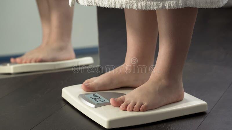 Peso adicional, hembra gorda en la albornoz que se coloca en escalas para comprobar resultados de la dieta fotos de archivo