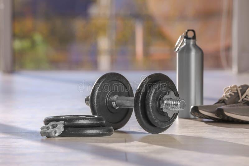 Peso ajustável com partes, garrafa e sapatilhas no assoalho dentro imagem de stock