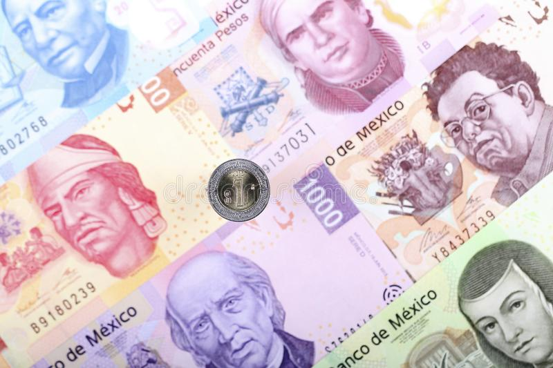 Peso coin on the background of Mexican banknotes stock image