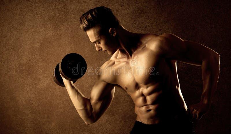Peso de elevación del ajuste del atleta muscular del culturista imagen de archivo libre de regalías