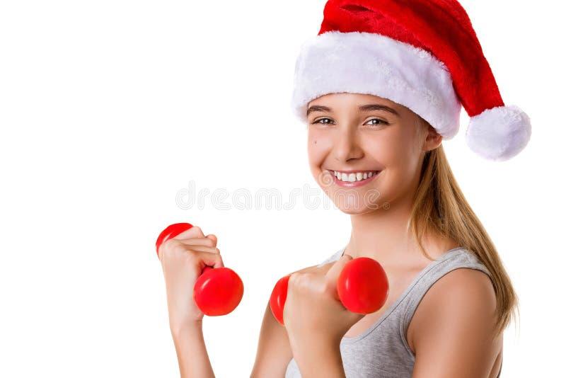 Peso de elevación de la mano del entrenamiento de la chica joven de la Navidad de la aptitud que lleva el sombrero de santa, aisl imagen de archivo libre de regalías