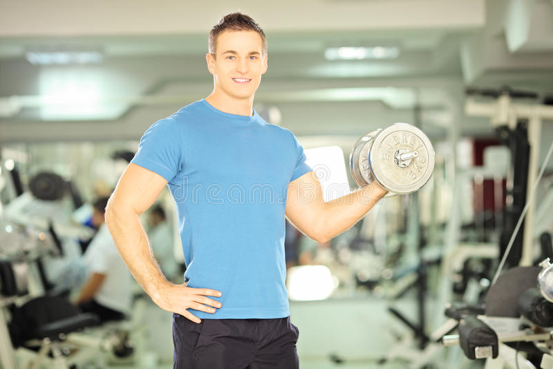 Peso de elevación sonriente del hombre muscular en club de fitness foto de archivo libre de regalías