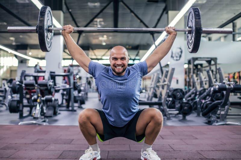Peso de elevación y griterío Hombre hermoso joven en barbell de elevaci?n de la ropa de deportes en el gimnasio fotos de archivo
