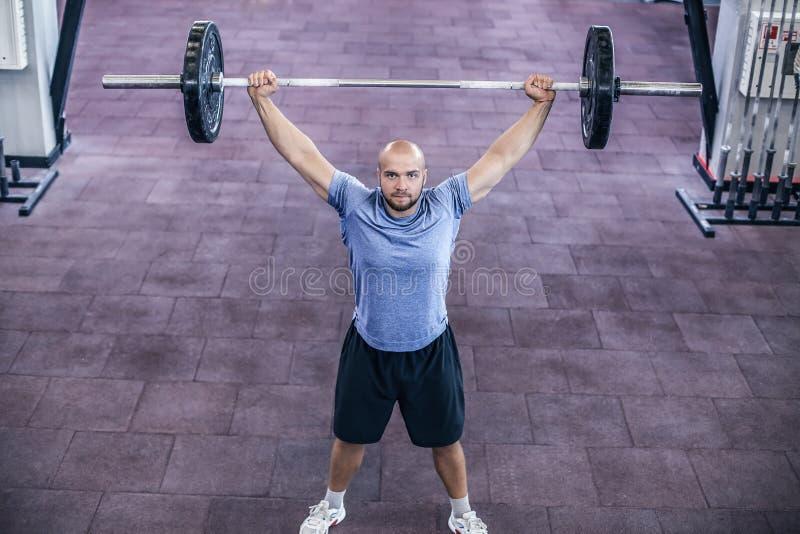 Peso de elevaci?n Hombre hermoso joven en barbell de elevaci?n de la ropa de deportes en el gimnasio foto de archivo