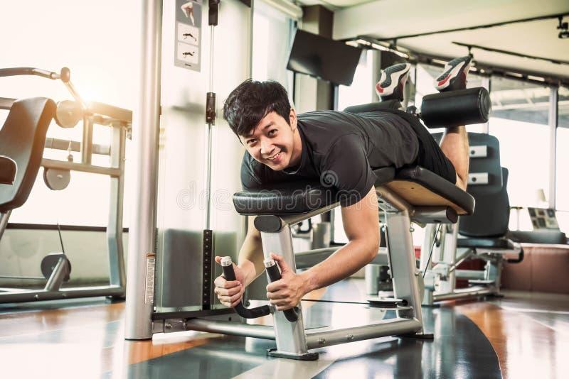 Peso de esticão e de levantamento do homem asiático do esporte por dois pés ao enfrentar para baixo para esticar o músculo no gym fotografia de stock