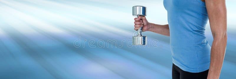 Peso de levantamento da mulher atlética do ajuste com brilho do fundo claro imagens de stock royalty free