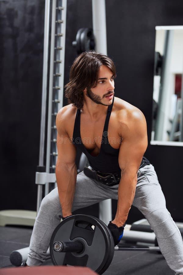 Peso de levantamento do barbell do homem farpado muscular foto de stock
