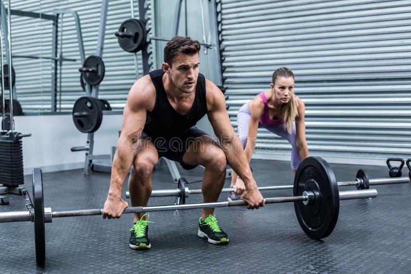 Peso de levantamento dos pares musculares junto foto de stock
