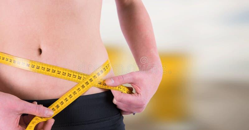 Peso de medição da mulher com a fita de medição na cintura na praia do verão imagens de stock royalty free
